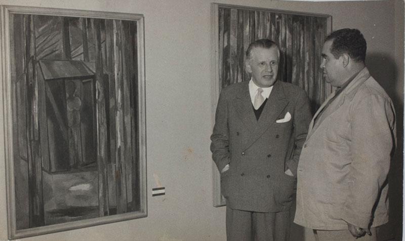 O artista Lasar Segall e o escritor e historiador pernambucano Benedito Geraldo Ferraz Gonçalves observam obras de Lasar Segall