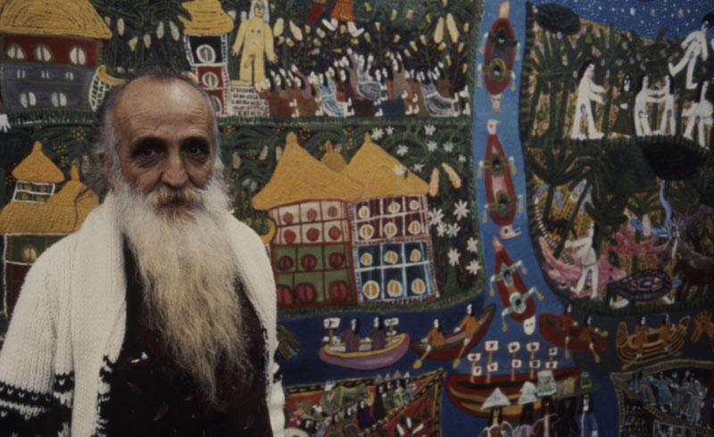 Retrato do artista Antonio Poteiro em frente à obra Adão e Eva no Brasil