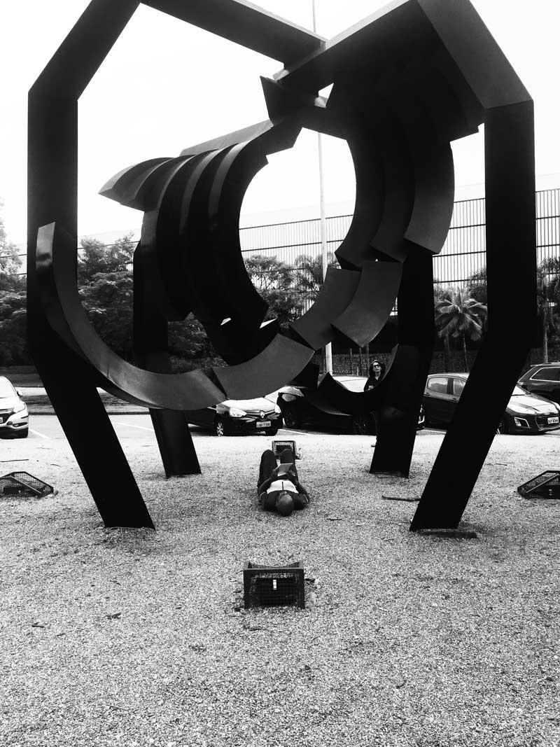Fotografia preto e branca de homem deitado no chão sob escultura abstrata de grande dimensão no Jardim das Esculturas do Museu de Arte Moderna de São Paulo no Parque do Ibirapuera. Ele está com as pernas dobradas e escreve com caneta em bloco de papel. Ao fundo há carros estacionados, árvores e o Pavilhão da Bienal.Sobre a imagem há o texto: Divulgadas as Ações de Difusão para o Biênio. No canto inferior direito há a legenda da imagem: Participante em exercício do laboratório de atenção da 33ª Bienal.