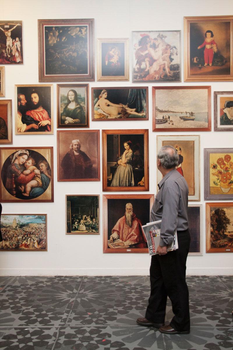 Visitante observa série de Fernando Bryce, Visión de la pintura occidental [Visão da pintura ocidental]