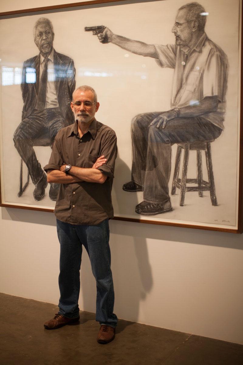 Retrato do artista Gil Vicente em frente à obra Autorretrato X – matando Kofi Annan (Série Inimigos)
