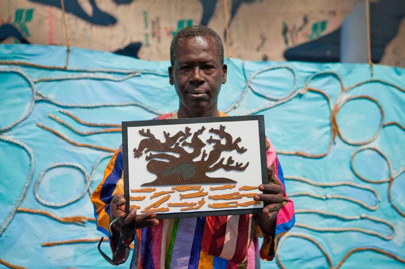 Retrato do artista El Hadji Sy em frente à obra Archéologie marine [Arqueologia Marinha]