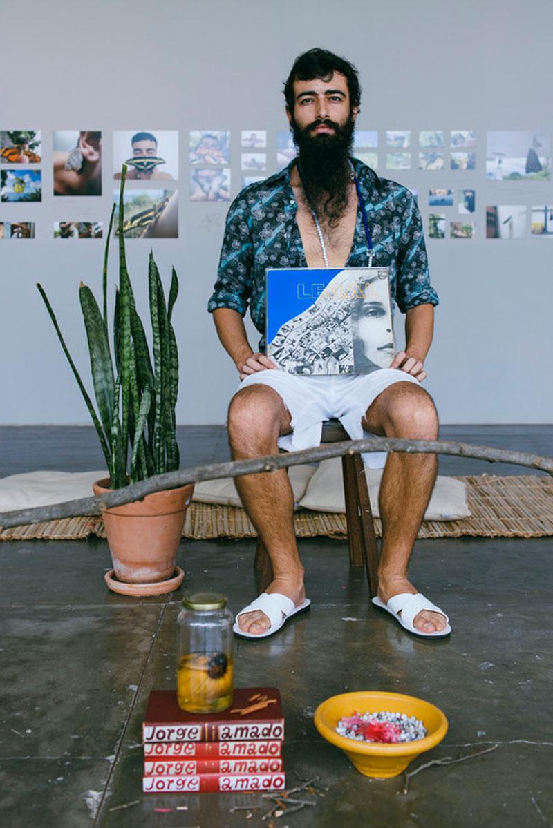 Retrato do artista Arthur Scovino em frente à obra Casa de Caboclo